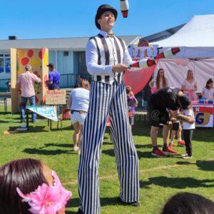 stilt-walker-juggling-clubs-fairground-male-stilt-walker-black-white-striped-costume-juggling-clubs-fair-159719329